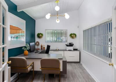 Modern office with table, cabinets, arm chairs, ceiling lamp and office machines